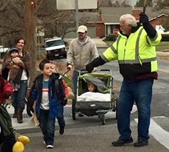 Crossing guard John Lewis, and families, crossing the street.